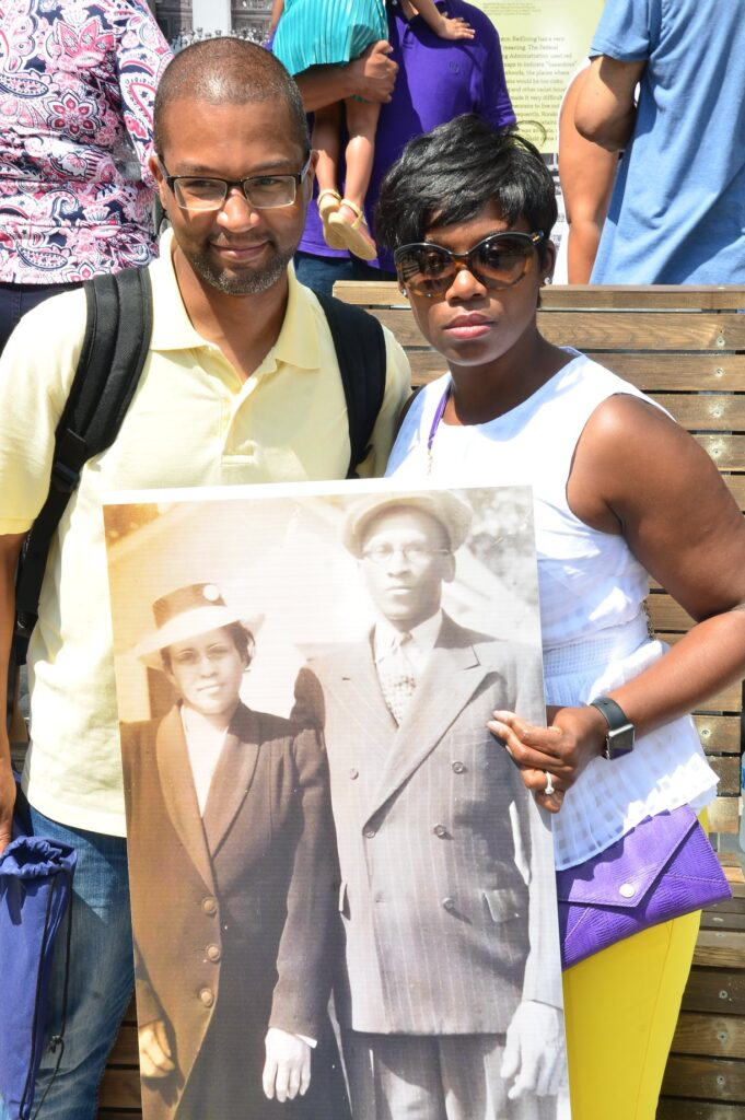 Two Rondo residents hold up a black and white picture of Rondo residents from decades ago at the new Rondo Community Center