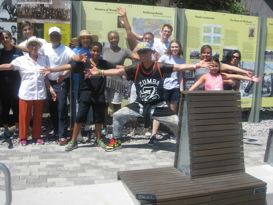 12 people with outstretched arms,smiling, at the unveiling of the Rondo Memorial Park