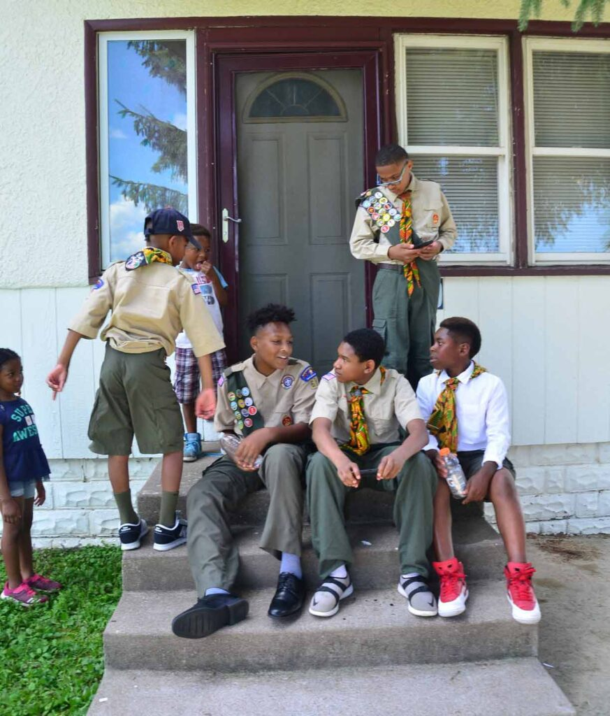 5 Boy Scouts sitting on the steps of a house in Saint Paul