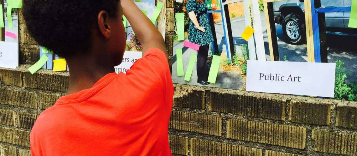 A boy looks at a display of public art on a brick wall at an outdoor festival in the Rondo neighborhood.
